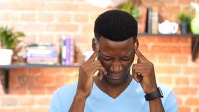 Kopfschmerzen, Frustration, deprimierter schwarzer junger Mann Lizenzfreie Stockbilder