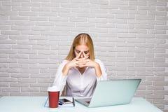Kopfschmerzen haben, nachdem wirklich harte Frau am BüroArbeitsplatz bearbeitet worden ist lizenzfreie stockfotografie