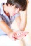 Kopfschmerzenmädchen mit Pillen in der Hand Lizenzfreie Stockbilder