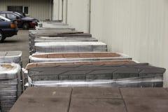 Kopfstein eingewickelt im Plastik, der auf hölzernen Paletten pflastert Lizenzfreie Stockbilder