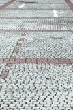 Kopfsteinpflasterung mit weißen Pfeilen Stockbild
