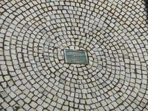 Kopfsteinpflasterungs-Radialmuster mit Dreckloch Stockbilder