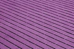 Kopfsteinsteinstraßenbelagmuster im purpurroten Ton Stockfotografie