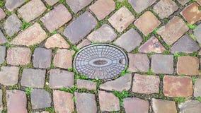 Kopfsteinstraße, zum von Untertagedienstprogrammen auszubrüten Brütet Abwasserkanal aus Lizenzfreies Stockbild