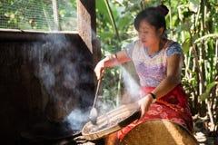 Kopi Luwak coffee burner. Indonesian woman burns the famous Kopi Luwak (Civet shit) coffee beans on the island Bali, Indonesia Royalty Free Stock Images