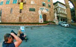 Kopian av Michelangelo ` s David på ingången av Palazzo Vecchio, flicka drar ståenden, fotograf skjuter berättelsen, Florence, Tu arkivfoton