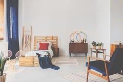 Kopienraum auf der weißen Wand des oldschool Jugendlichschlafzimmers mit Holzmöbel und dunkelblauen Akzenten lizenzfreies stockbild