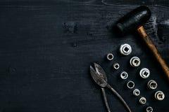 Kopiera utrymme av funktionsdugliga hjälpmedel på en svart träyttersida Pojkar skiftnyckeltangenter, plattång, skruvmejsel, hamma Royaltyfri Foto