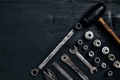 Kopiera utrymme av funktionsdugliga hjälpmedel på en svart träyttersida Pojkar skiftnyckeltangenter, plattång, skruvmejsel, hamma Arkivfoto