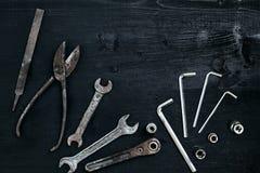 Kopiera utrymme av funktionsdugliga hjälpmedel på en svart träyttersida Pojkar skiftnyckeltangenter, plattång, skruvmejsel Top be Arkivfoto