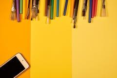 Kopiera utrymme med borstar och mångfärgade pennor på guling Royaltyfri Fotografi