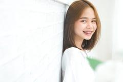 Kopiera utrymmeståenden av att le den pålagda asiatiska unga kvinnan hänglsen, på vit bakgrund royaltyfri bild