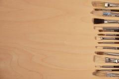 Kopieren Sie Raum auf Holz mit vielen Bürsten auf der Seite Lizenzfreie Stockfotos