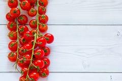 Kopieren Sie Raumbild Feld von hellen roten Kirschtomaten an der Niederlassung am weißen hölzernen Hintergrund lizenzfreie stockfotografie