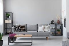 Kopieringsutrymme på väggen av scandinavian vardagsrum med den moderna soffan, metallhyllor och den industriella kaffetabellen arkivbilder