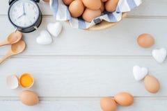 Kopieringsutrymmeram för text på det vita köksbordet med nya rå ägg, ägg för gul äggula, det vita hjärtaformtecknet och klassisk  royaltyfri foto
