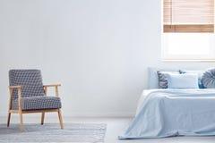 Kopierter Lehnsessel auf Teppich im minimalen Schlafzimmerinnenraum mit Querstation stockfoto