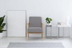 Kopierter Lehnsessel nahe bei leerem Plakat in weißem flachem Innenraum w Lizenzfreie Stockbilder