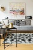 Kopierter Teppich und Kissen auf grauem Sofa im modernen Wohnzimmer lizenzfreies stockbild