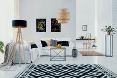 Kopierter Teppich und Lampe im weißen Wohnzimmerinnenraum mit Poster über Sofa mit Kissen Reales Foto lizenzfreie stockbilder