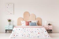 Kopiertes Bett mit Kopfende zwischen rosa und blauem Kabinett in ist stockbilder