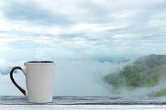 Kopkoffie en thee met stoom op houten lijst over het landschap van de bergenstad met de winter van het mistzonlicht De achtergron stock foto's