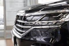 Koplamp van nieuwe zwarte auto in het handel drijventoonzaal stock afbeeldingen