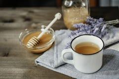 Kopp av örtte med vis man och honung med skeden i nolla för glass bunke royaltyfria foton
