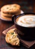 Kopp av cafeaulait och pistaschkakan Arkivbild