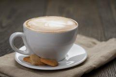 Kopp av cappuccino med hem- kakor Arkivfoton