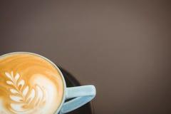 Kopp av cappuccino med kaffekonst på trätabellen Fotografering för Bildbyråer
