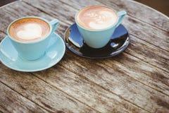 Kopp av cappuccino med kaffekonst på trätabellen Arkivbilder