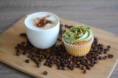 Kopp av cappuccino med muffin- och kaffebönor Royaltyfri Foto