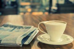 Kopp av cappuccino med tidningen på tabellen in i morgonen royaltyfri foto