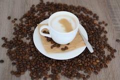 Kopp av cappuccino- och kaffebönor Arkivfoton