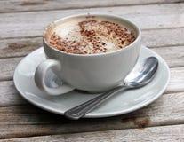 Kopp av Cappuccino på träslattabellen Royaltyfri Bild