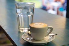 Kopp av cappuccinoexponeringsglas av vatten Arkivfoto