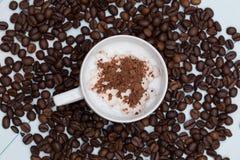 Kopp av cappuccinokaffe med bönor Arkivfoto
