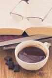 Kopp av choklad på en trätabell med böcker Fotografering för Bildbyråer