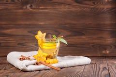 Kopp av citronte med mintkaramellen på en träbakgrund Sött, varmt och sunt grönt te Te med carambolaen och kanel kopiera avstånd royaltyfri fotografi