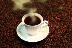 Kopp av cofee på kaffehjärnor. Arkivfoton