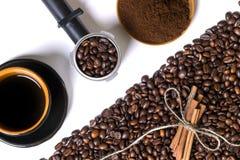 Kopp av coffe, korn av kaffe, jordkaffe och kanel på en vit bakgrund Arkivfoto