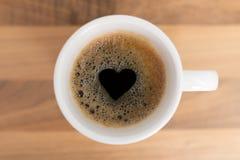 Kopp av coffe med hjärtaform i skum Arkivfoto