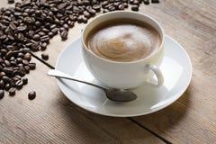 Kopp av coffe på ett tefat med en tappningsked Fotografering för Bildbyråer