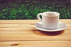 Kopp av coffe på trätabellen i trädgård Royaltyfri Foto