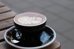 Kopp av coffecapucine i svart kopp med förbindelse av staden Arkivbild