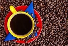Kopp av colombianskt kaffe och färgerna av den colombianska flaggaoven arkivfoto