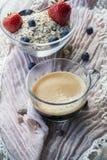 Kopp av den svarta glass bunken för kaffe och med flingor, bär och en sked Royaltyfria Bilder