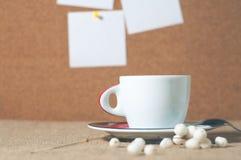 Kopp av den varma drinken med kaffebönor Arkivbild