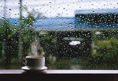 Kopp av den varma drinken på trätabellen i regnig dag Royaltyfri Bild